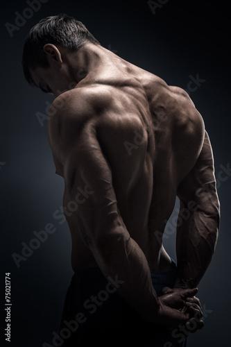Photo Handsome muscular bodybuilder turned back