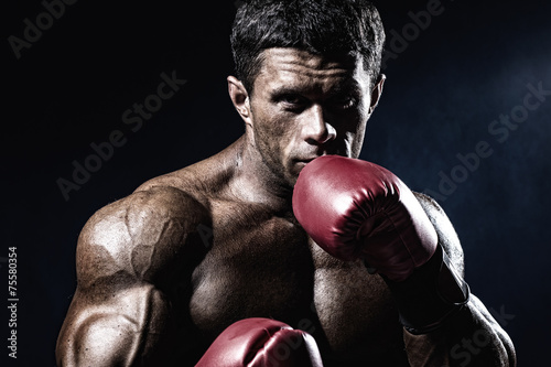 Canvas Print Strong muscular boxer in red boxing gloves. A man in a boxing st
