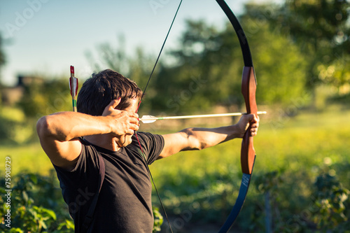Canvas Print Young archer training with the  bow