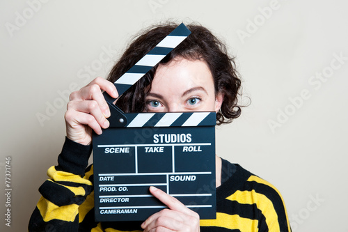Photo Smiling girl with movie clapper on white background