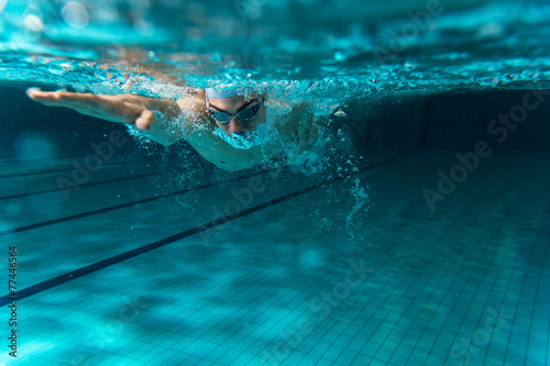 Canvas Print Male swimmer at the swimming pool.Underwater photo.