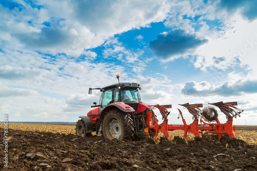 Canvas Print Farmer plowing stubble field with red tractor