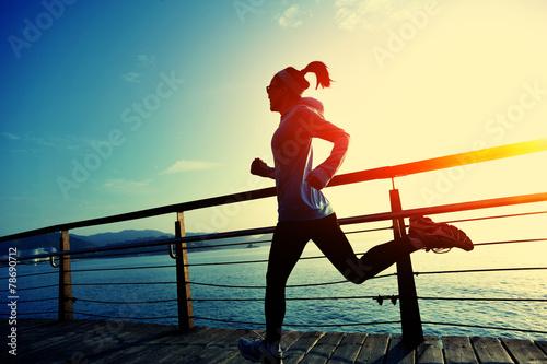 young fitness woman running on seaside boardwalk Fototapeta