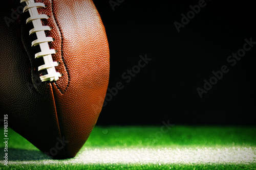 Canvas Print American football on green grass, on black background