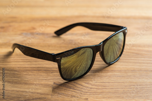 Black sunglasses on a wooden table