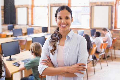 Fotografie, Obraz Pretty teacher smiling at camera at back of classroom