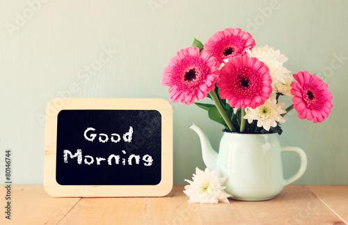 Valokuva blackboard with the phrase good morning written on it next to va