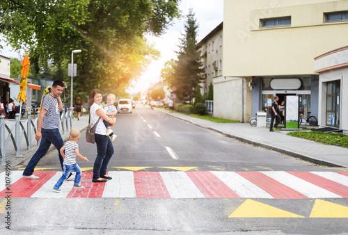 Leinwand Poster Junge Familie mit zwei Jungen in der Stadt, die auf einen Zebrastreifen geht