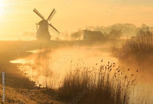 Obraz na płótnie Windmill during a foggy, yellow sunrise in the countryside.