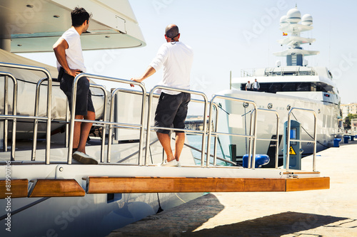 Fotomural Yacht crew at port, on the boat ramp, looking to an exclusive yacht