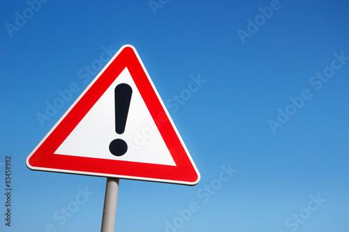 Fototapeta Warning road sign against a blue sky.