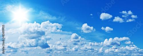 Fototapeta Białe, pojedyncze chmury i jaskrawe słońce w niebieskim niebie panoramiczna