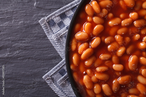 beans in tomato on a plate close-up. horizontal top view