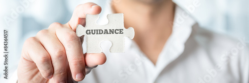 Photo Businessman Holds Puzzle Piece with Guidance Text