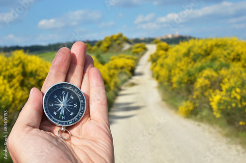 Canvas Print Compass in the hand against rural road