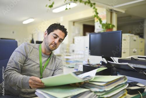 Foto Büroangestellter, der Dateien im Büro liest