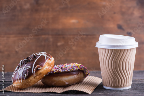 fresh artisan donuts and take away coffee, wooden background