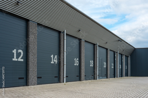 Fototapeta Row of gray numbered business units or garages