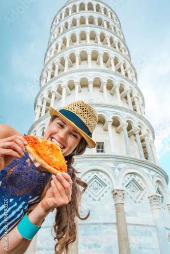 Photo Woman biting slice of pizza by Leaning Tower of Pisa
