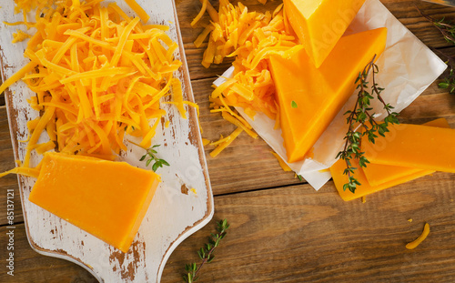Cheddar Cheese on white wooden cutting Board.