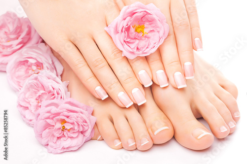 Relaxing pedicure and manicure with a pink rose flower