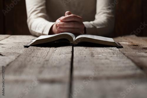 Fotografie, Obraz Žena ruce se modlí s Biblí v temnotě přes dřevěný stůl