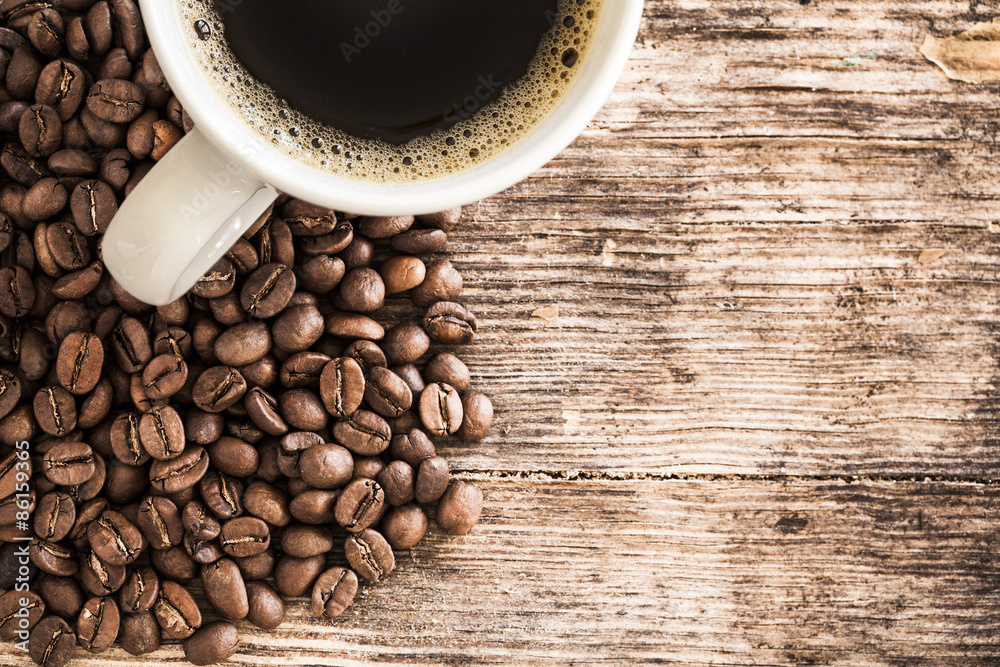 Coffee cup and beans on a wooden table