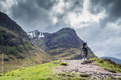 Traditional scottish bagpiper in full dress code in the highlands Fotobehang