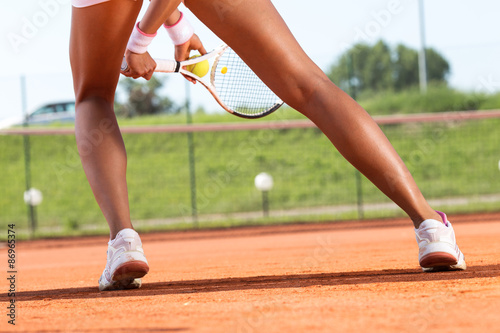 Canvas Print Legs of female tennis player.Close up image.
