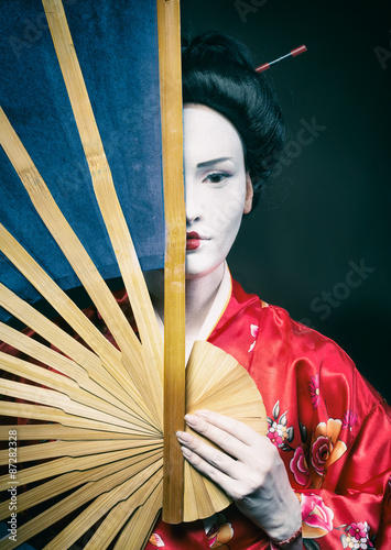 Fotografia Woman in geisha makeup covering half of her face with a big fan