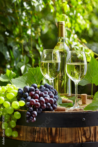The glass of wine an and old barrel and grape
