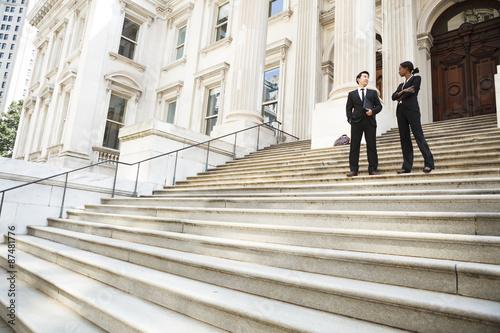 Tableau sur Toile Un homme et une femme converse bien habillé sur les marches d'un édifice juridique ou municipal