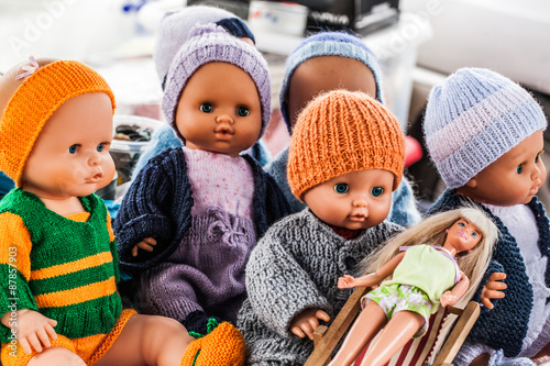display of old plastic dolls and baby dolls wearing home-made knitwear sold at f Fototapeta