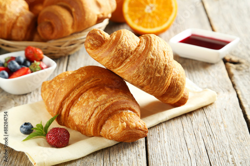 Fotografia Fresh tasty croissants with berries on grey wooden background