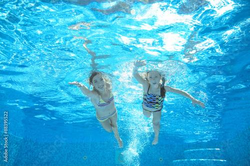 Canvas Print Children swim in pool underwater, happy active girls have fun in water