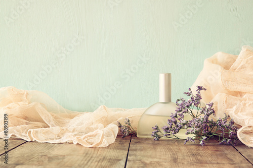 Leinwand Poster vintage perfume next to flowers on wooden table