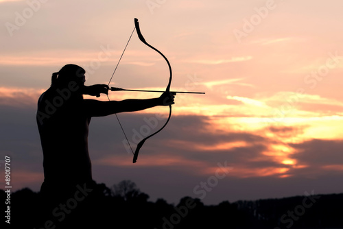 Silhouette archery shoots a bow at a target in sunset sky Fototapeta