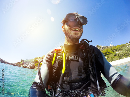 Smiling diver portrait at the sea shore. Diving goggles on.