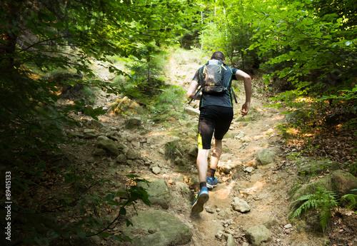 Fototapeta trail runner with backpack running up the steep hill