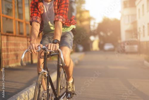 Zamyka w górę modnisia na rowerze w mieście przy zmierzchem. Strzał z