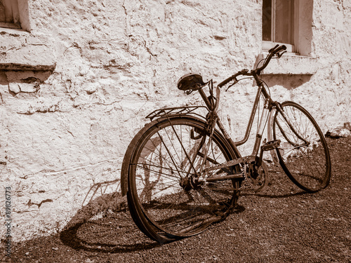 Sepia image of broken old bicycle leaning against white-washed stone wall of building #89826773