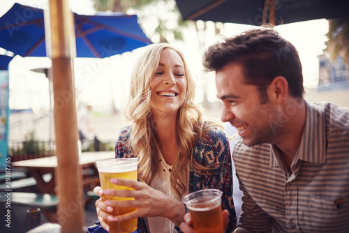 Fotografiet happy couple having a good time drinking beer together at outdoor pub or bar