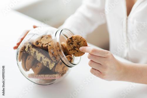 Fotografija close up of hands with chocolate cookies in jar