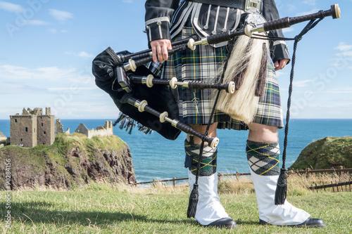Fotografía Traditional scottish bagpiper in full dress code at Dunnottar Castle in Stonehav