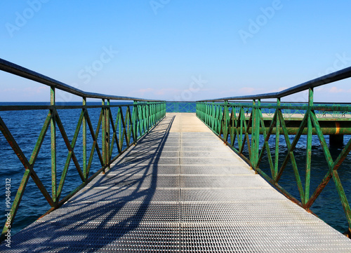 Pier at the sea with green railing