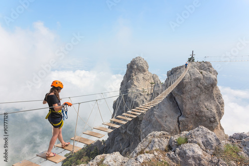 Canvastavla Young woman crossing the chasm on the rope bridge