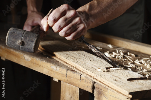 carpenter hands working with a chisel and hammer Fototapeta