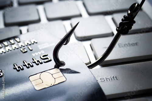 Canvas credit card phishing - piles of credit cards with a fish hook on computer keyboa