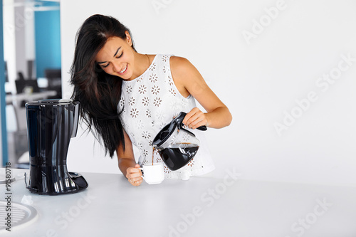 Cuadros en Lienzo Photo of a woman pouring coffee from a glass pot