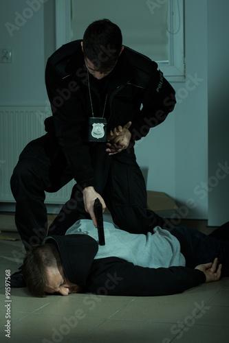 Fototapeta Police officer overpowering a criminal